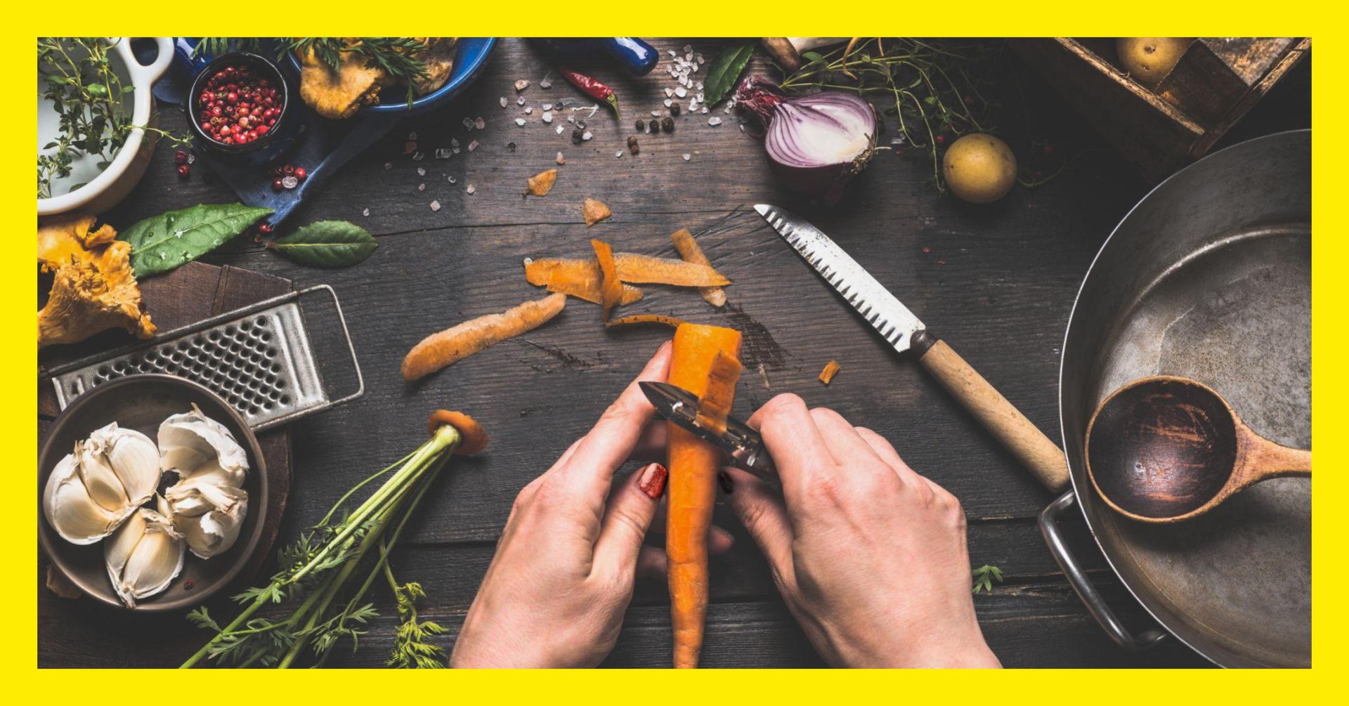 kädet kuorimassa porkkanaa, pöydällä vihanneksia