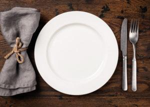 pöydällä kattaus, tyhjä lautanen, aterimet ja servetti